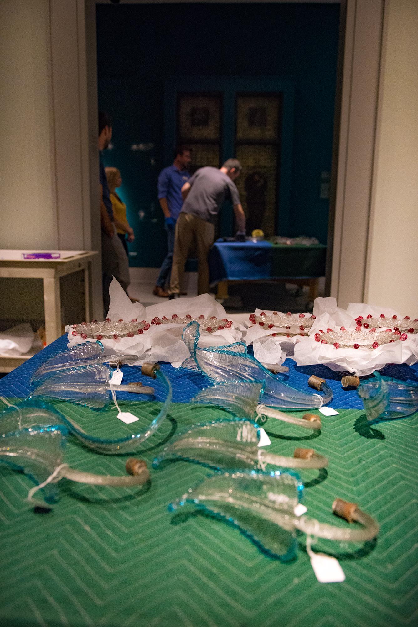 staff members taking down a salviati glass piece
