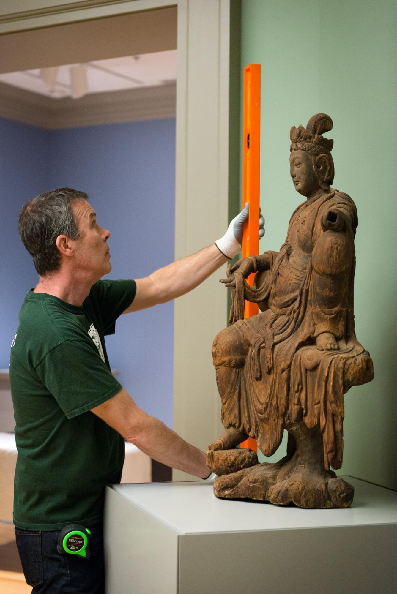 a staff member installing a sculpture