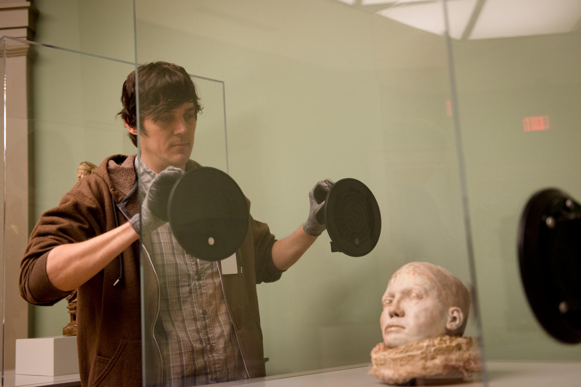 a staff member sealing a sculpture in a glass fixture