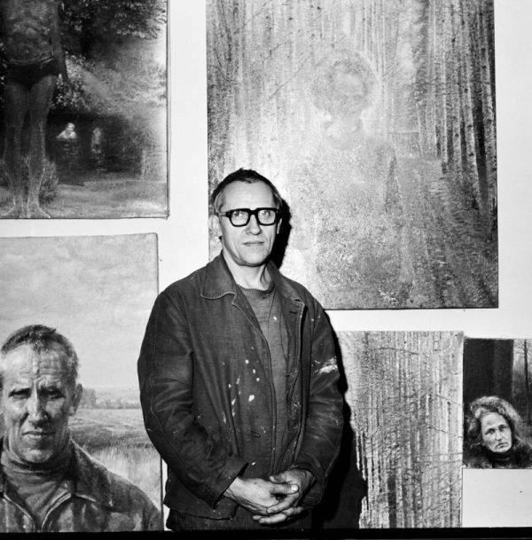 Artist Oleg Vassiliev standing with paintings